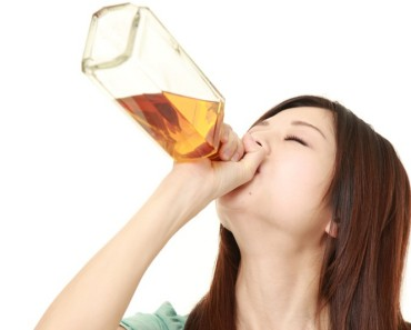Woman downing alcohol